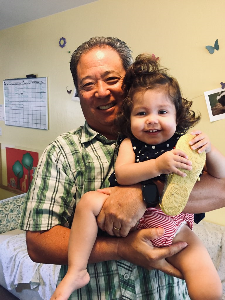 Dr Dave Violet holding his daughter and smiling