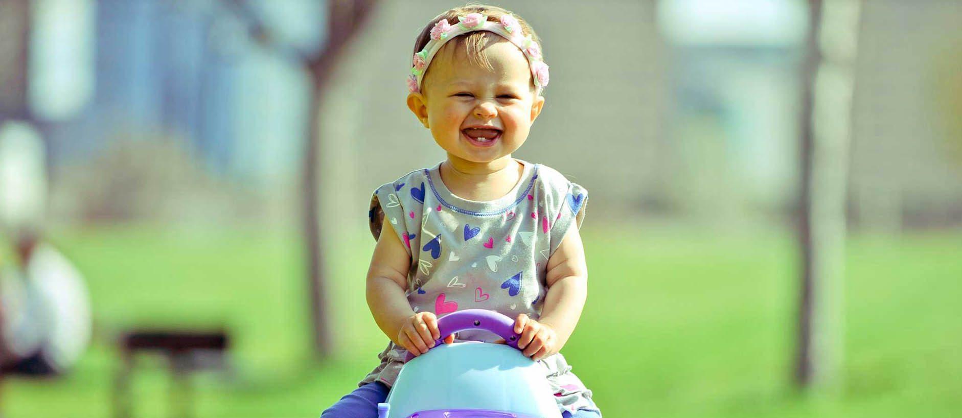 Toddler girl on plastic car laughing
