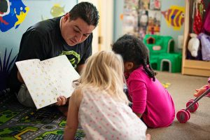 Man teaching two toddler girls in preschool