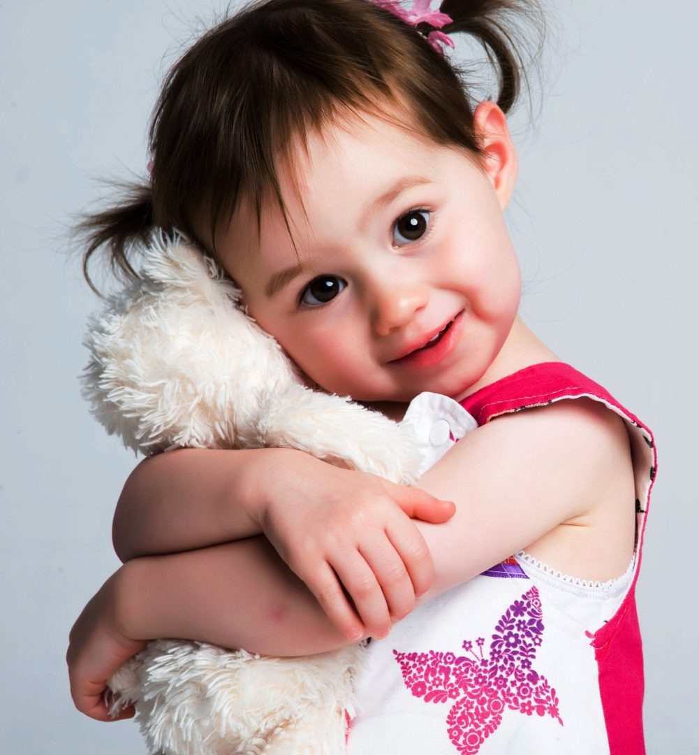 Adorable baby girl hugging her teddy bear