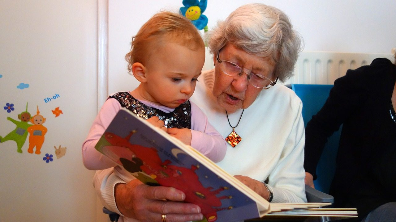 Retired volunteer reading to a child on a sofa